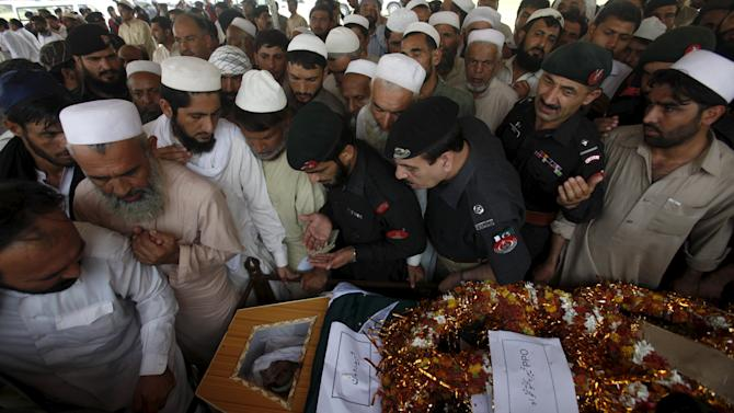 Security officials and relatives gather around the flag-draped coffin of a policeman after his funeral prayers in Peshawar
