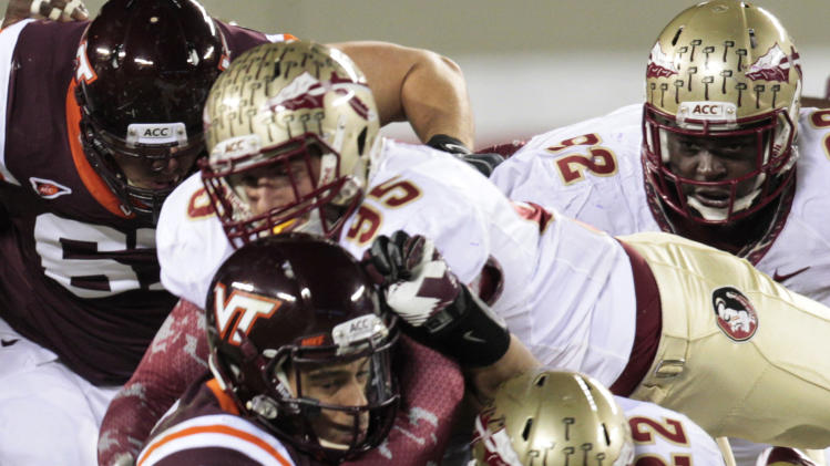 Virginia Tech quarterback Logan Thomas (3) is sacked by Florida State linebacker Telvin Smith (22) and defensive end Bjoern Werner (95) during the first half of an NCAA college football game in Blacksburg, Va., Thursday, Nov. 8, 2012. (AP Photo/Steve Helber)