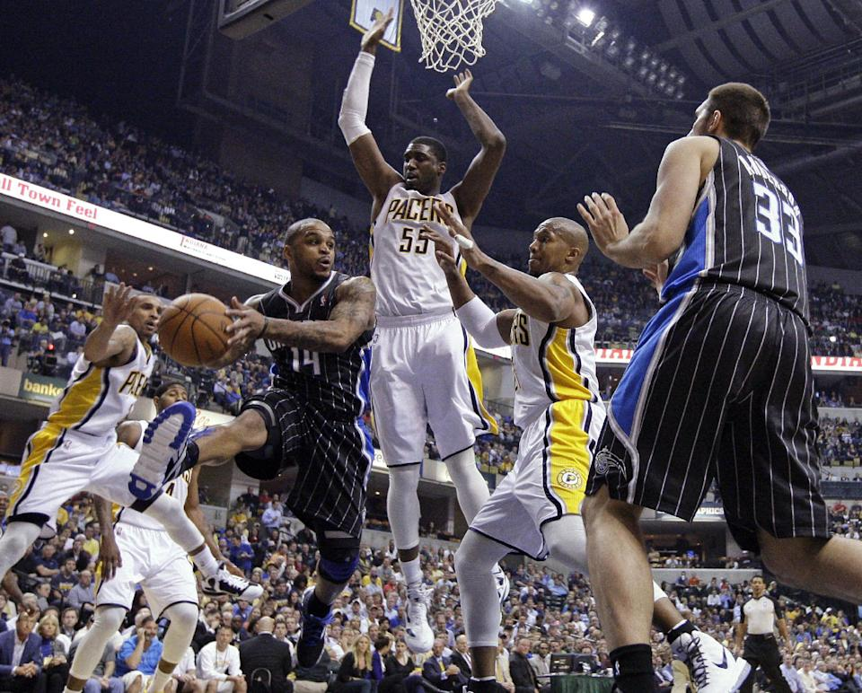 Orlando Magic guard Jameer Nelson (14) makes a pass against Indiana Pacers center Roy Hibbert, center, and guard Leandro Barbosa during the first half of the second game of an NBA first-round playoff basketball series, in Indianapolis on Monday, April 30, 2012. (AP Photo/Michael Conroy)