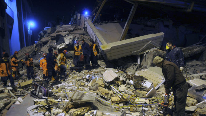 Rescuers search for survivors in the rubble of a collapsed hotel in Van, eastern Turkey, late Wednesday, Nov. 9, 2011.  An earthquake struck eastern Turkey on Wednesday night, killing at least three people and leaving dozens trapped in the rubble of toppled buildings damaged in the previous temblor, which had killed 600 people. About 20 buildings collapsed in the provincial capital of Van following a 5.7-magnitude quake, according to media reports.(AP Photo/Evrim Aydin, Anatolia) TURKEY OUT