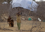 A child, center, plays with a kite made from string and plastic in a displacement camp in Dadaab, Kenya, Sunday, July 31, 2011. Dadaab, a camp designed for 90,000 people now houses around 440,000 refugees. Almost all are from war-ravaged Somalia. Some have been here for more than 20 years, when the country first collapsed into anarchy. But now more than 1,000 are arriving daily, fleeing fighting or hunger.(AP Photo/Schalk van Zuydam)