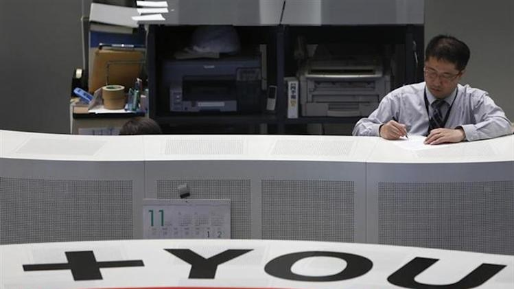 A Tokyo Stock Exchange (TSE) staff member works at the bourse at TSE in Tokyo November 14, 2013.