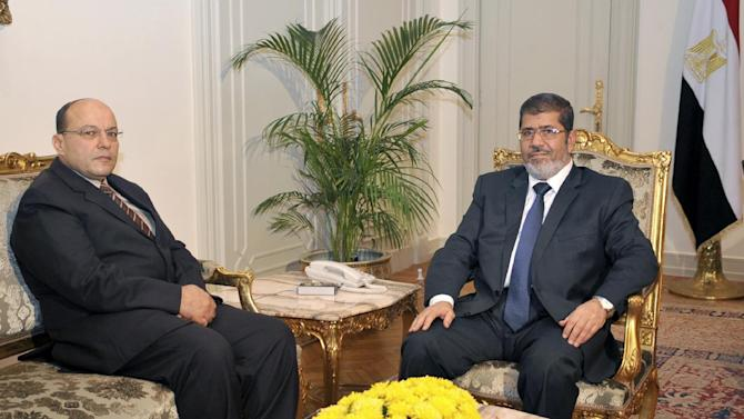 In this photo released by the Egyptian Presidency, President Mohammed Morsi, right, poses for a photograph with his new Prosecutor General, Talaat Abdullah, left, in Cairo, Egypt, Thursday, Nov. 22, 2012. Egypt's president on Thursday issued constitutional amendments granting himself far-reaching powers and ordering the retrial of leaders of Hosni Mubarak's regime for the killing of protesters in last year's uprising. Morsi also on Thursday fired the country's top prosecutor by decreeing with immediate effect that he could only stay in office for four years and replacing him with Talaat Abdullah. Morsi fired Abdel-Maguid Mahmoud for the first time in October, but had to rescind his decision when he found that the powers of his office do not empower him to do so. (AP Photo/Egyptian Presidency)