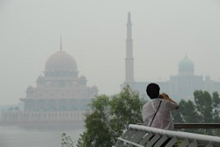 A visitor takes pictures with the Putra Mosque (left) and the Malaysian Prime Minister's office in Putrajaya, outside Kuala Lumpur on June 26, 2013. — AFP pic
