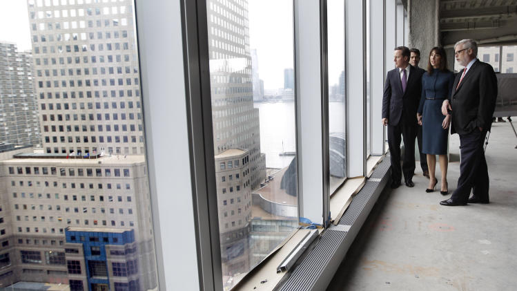 British Prime Minister David Cameron, left, and his wife Samantha, center,  look over the World Trade Center site during a tour of the 21st floor of the 1 World Trade Center with Port Authority of NY and NJ Executive Director Patrick J. Foye, Thursday, March 15, 2012 in New York.  (AP Photo/Mary Altaffer, Pool)