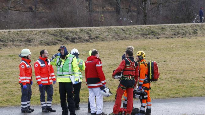 Members of rescue services stand on a road near Bad Aibling