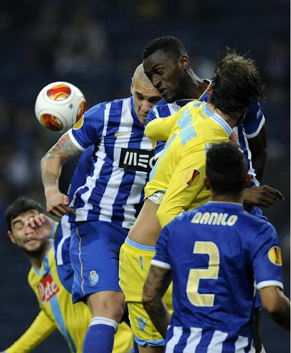 Napoli's Henrique Buss, second right, challenges for a high ball with FC Porto's Jackson Martinez, centre, and Maicon Roque, from Brazil, during their Europa League round of 16, first leg socc