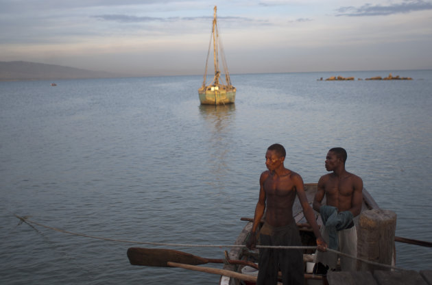 Fishermen arrive in a rowboat to Port Cite Soleil in Port-au-Prince, Haiti, Friday, Aug. 24, 2012. Tropical Storm Isaac strengthened slightly as it spun toward the Dominican Republic and Haiti, but seemed unlikely to gain enough steam early Friday to strike as a hurricane. The storm's failure to gain the kind of strength in the Caribbean that forecasters initially projected made it more likely that Isaac won't become a hurricane until it enters the Gulf of Mexico, said Eric Blake, a forecaster with U.S. National Hurricane Center in Miami. (AP Photo/Dieu Nalio Chery)