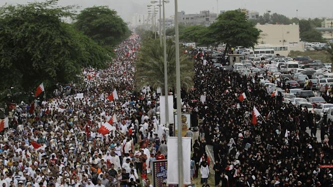 """Bahraini anti-government protesters stretch for more than 5 kilometers (3 miles) along a main four-lane divided highway Friday, May 18, 2012, west of the capital of Manama, Bahrain. Tens of thousands of protesters chanting """"Bahrain is not for sale"""" denounced proposals for closer unity between the unrest-torn Gulf kingdom and neighboring Saudi Arabia. (AP Photo/Hasan Jamali)"""