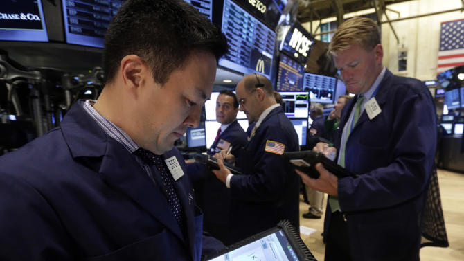 Trader John Song, left, works on the floor of the New York Stock Exchange, Monday, June 10, 2013. The stock market is getting off to a mixed start as traders show only mild enthusiasm for an improving outlook for the U.S. government's credit rating. (AP Photo/Richard Drew)