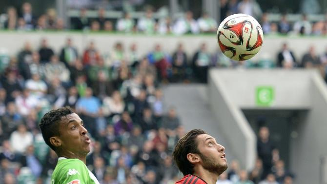 Leverkusen's Calhanoglu and VfL Wolfsburg's Malanda fight for the ball during the German Bundesliga first division soccer match in Wolfsburg