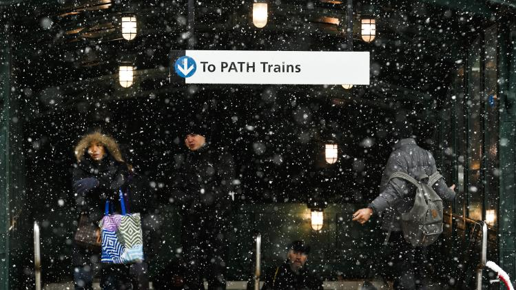People exit the path station during the arrival of a snowstorm in Hoboken, New Jersey
