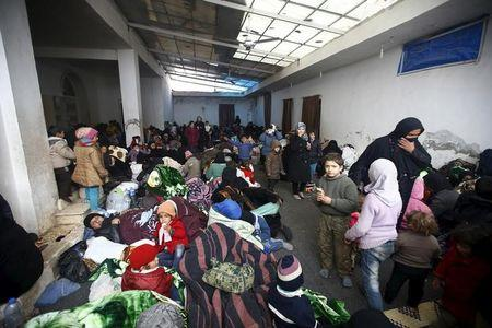 Internally displaced Syrians gather at a shelter near the Bab al-Salam crossing, opposite the Turkey's Kilis province
