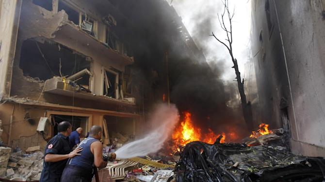 Lebanese firefighters extinguish burning cars at the scene of an explosion in the mostly Christian neighborhood of Achrafiyeh, Beirut, Lebanon, Friday Oct. 19, 2012. (AP Photo/Hussein Malla)