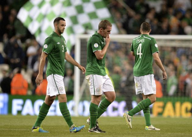 Ireland's Wilson, Dunne and O'Shea leave the pitch after losing their World Cup qualifying match against Sweden in Dublin