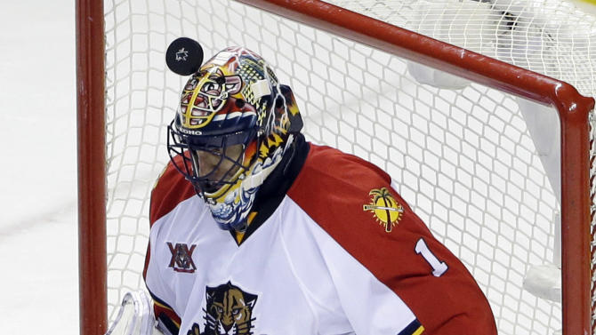 Florida Panthers goalie Roberto Luongo stops a shot with his helmet during the third period of an NHL hockey game against the San Jose Sharks on Tuesday, March 18, 2014, in San Jose, Calif. Florida won 3-2