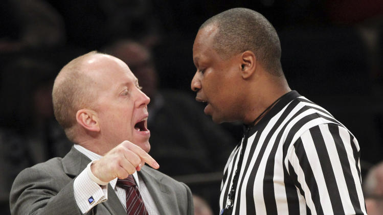 Cincinnati coach Mick Cronin, left, argues with a referee during the first half of an NCAA college basketball game against Georgetown at the Big East Conference tournament, Thursday, March 14, 2013 in New York. (AP Photo/Mary Altaffer)