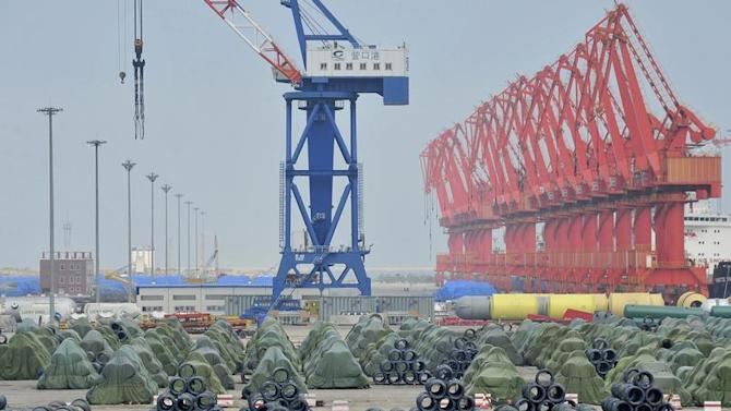 A worker rides his bicycle past piles of steel coils for export at a port in Yingkou