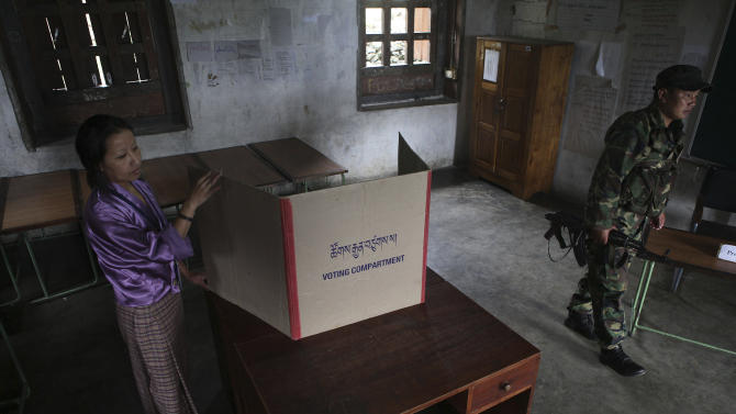A Bhutanese woman arranges a polling booth on the eve of polling to the upper house National Council in Samdrup Jonkhar, Bhutan, Monday, April 22, 2013. The small Himalayan country of Bhutan ended more than a century of absolute monarchy by holding its first parliamentary elections in 2008. (AP Photo/Anupam Nath)