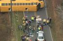 In this image made from video and released by WSOC-TV, authorities render aid to school children, Wednesday, Jan 14, 2014, in Gastonia, N.C. A school bus carrying about 40 students overturned in Gaston County Wednesday afternoon, according to WSOC. (AP Photo/WSOC-TV) MANDATORY CREDIT WSOC-TV
