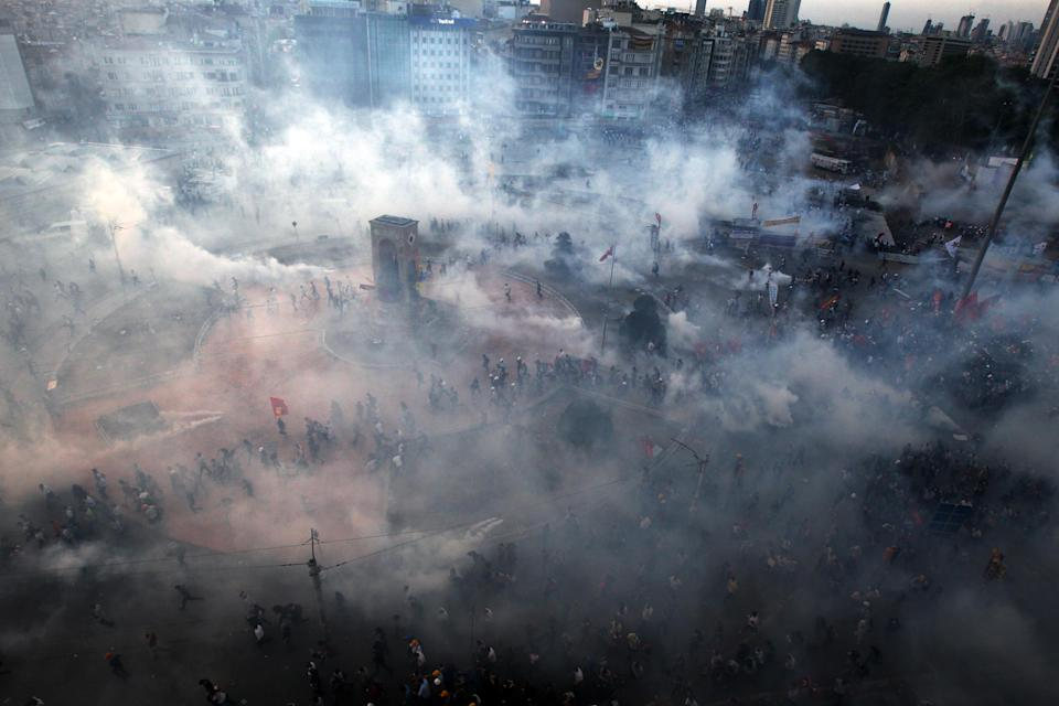 FILE - In this Tuesday, June 11, 2013, file photo, protesters run to avoid the tear gas during clashes at the Taksim Square in Istanbul. (AP Photo/Thanassis Stavrakis)
