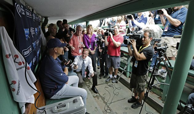 Cleveland Indians manager Terry Francona, left, is surrounded by members of the media in the visitor's dugout before a baseball game against the Boston Red Sox at Fenway Park in Boston, Thursday, May