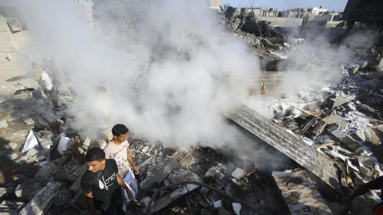 Smoke rises as Palestinians stand atop the rubble of a house, which witnesses said was destroyed in an Israeli air strike, in Rafah in the southern Gaza Strip