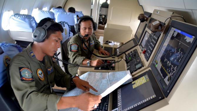 Members from the Indonesian Navy's Tactical Commanding Operator help with the search for AirAsia flight QZ 8501on board a CN235 aircraft over Karimun Java in the Java Sea
