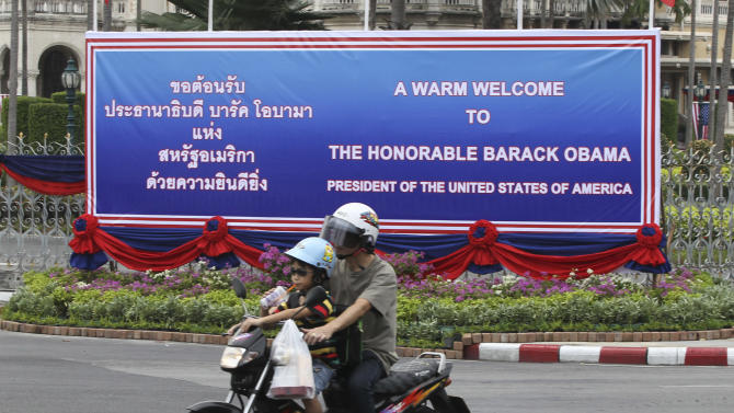 A man rides on a motorbike with a child past a welcoming banner for U.S. President Barack Obama erected outside the government house in Bangkok, Thailand Saturday, Nov. 17, 2012. Obama will arrive in Thailand on Sunday, Nov. 18, 2012 as part of his southeast Asian nations tour which includes Myanmar and Cambodia. (AP Photo/Apichart Weerawong)