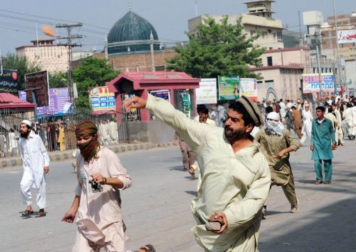 Pakistani Muslim demonstrators throw stones toward police during a protest against an anti-Islam film in Peshawar. At least 15 died in protests around the country