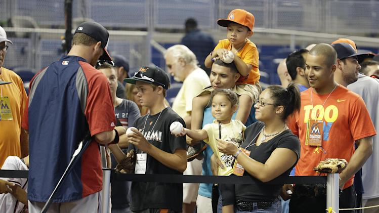 Fans wait for autographs by Washington Nationals first baseman Adam LaRoche, left, during batting practice before a baseball game against the Miami Marlins, Tuesday, July 29, 2014, in Miami. (AP Photo/Lynne Sladky)