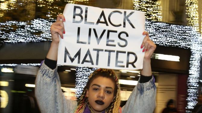 A protester marches to show her solidarity with the family of black teenager Michael Brown outside the American Embassy in London