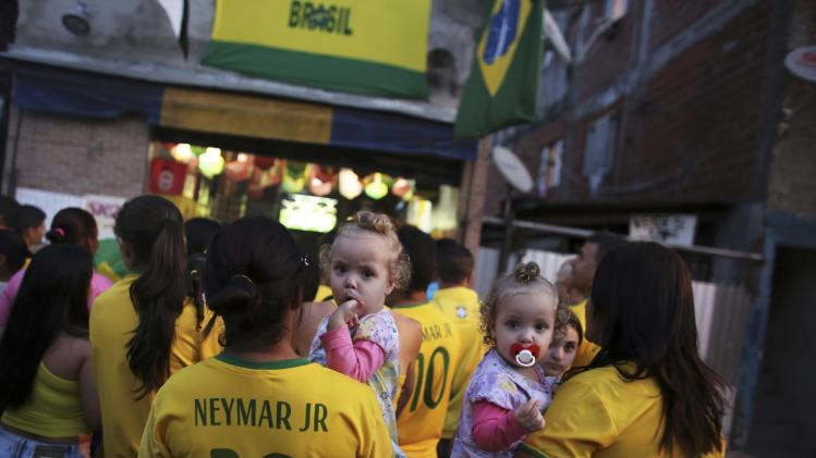 Brazilian soccer fans watch their team play against Cameroon during the 2014 World Cup Group A soccer match at the Corrilhos favela in Sao Paulo