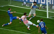 Croatian forward Mario Mandzukic (C) scores past Italian goalkeeper Gianluigi Buffon (top) during a Euro 2012 championships football match at the Municipal Stadium in Poznan. Mandzukic's third goal of Euro 2012 saw Croatia come from behind to draw 1-1 with Italy in their Group C match here on Thursday
