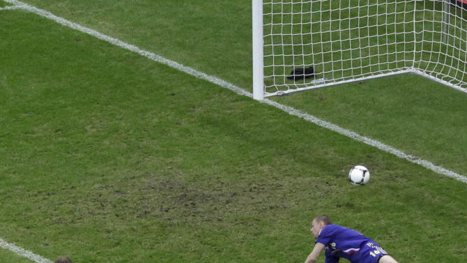Greece's Giorgos Karagounis, front, scores the opening goal past Russia goalkeeper Vyacheslav Malafeev during the Euro 2012 soccer championship Group A  match between Greece and Russia in Warsaw, Poland, Saturday, June 16, 2012. (AP Photo/Gero Breloer)