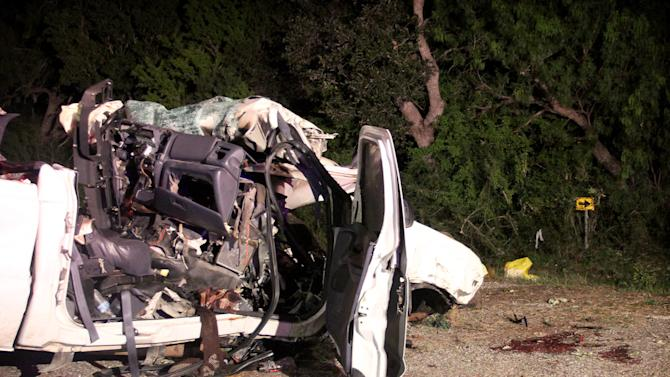 This July 22, 2012, photo shows a pickup truck that authorities say was overloaded with passengers  when it veered off a highway and crashed into trees near Goliad, Texas, killing at least 13 people and injuring 10. Officials said at least 23 passengers were crammed inside the truck's cab and bed, including at least two young children.  (AP Photo/The Victoria Advocate, Angeli Wright)