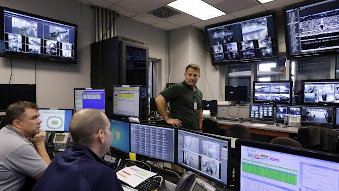 In this Oct. 15, 2014, photo, Daniel DeLorenzi, right, director of security and safety services at MetLife Stadium, talks with others in the stadium's command center in East Rutherford, N.J. Suppose a shoving match breaks out in a section of the MetLife Stadium stands. While security officers hustle to the scene, a beyond state-of-the-art surveillance system is recording every detail