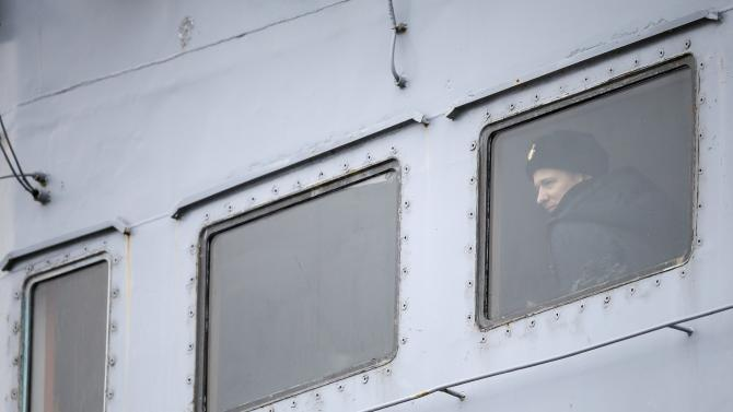 A Russian sailor looks through a window of the Russian Navy frigate Smolny as the ship leaves the STX Les Chantiers de l'Atlantique shipyard site in Saint-Nazaire