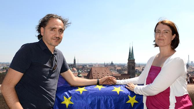 Greek-born German Anestis Aslanidis and his German wife Bettina Zauhar pose for a photo with the European flag, at the Nuremberg Castle in southern Germany