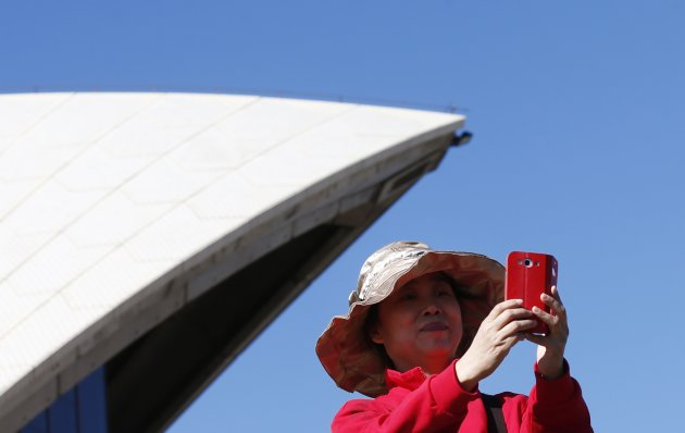 A Chinese tourist takes a picture from the steps of the Sydney Opera House in Sydney