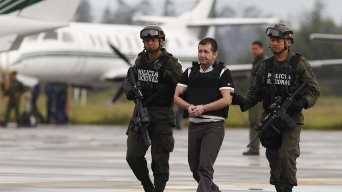 """Major drug trafficking suspect, Daniel Barrera is escorted to a waiting car, prior to his extradition to the U.S., at the counter-narcotics base in Bogota, Colombia, Tuesday, July 9, 2013. Colombian President Juan Manuel Santos has called Barrera """"the last of the great capos."""" He's known as """"El Loco,"""" Spanish for """"The Madman."""" Barrera is wanted in two New York federal court districts on charges related to drug trafficking. He also faces charges in Florida. (AP Photo/Fernando Vergara)"""