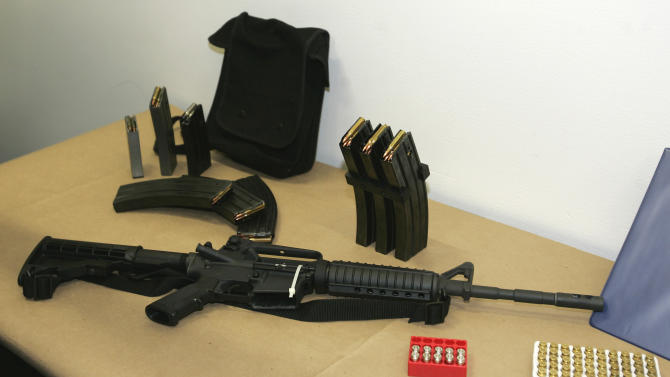 FILE - This March 27, 2006 file photo, shows a Bushmaster AR-15 semi-automatic rifle and ammunition on display at the Seattle Police headquarters in Seattle. The maker of the Bushmaster rapid-fire weapon used to kill schoolchildren in Connecticut on Friday, Dec. 14, 2012, was put up for sale on Tuesday, Dec. 18, 2012, as investors soured on the gun business. (AP Photo/Ted S. Warren, File)