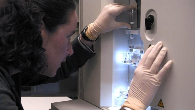 In this image provided by the National Human Genome Research Institute, a NHGRI researcher monitors a DNA sequencing machine at the NIH in Bethesda, Md. A presidential commission says new protections to ensure the privacy of people's genetic information are critical if the nation is to realize the enormous medical potential of gene-mapping.  (AP Photo/National Human Genome Research Institute, Maggie Bartlett)
