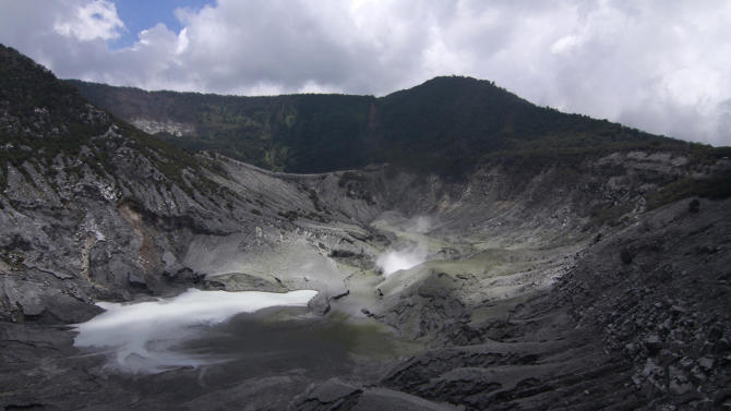Volcanic smoke spews from the crater of Tangkuban Perahu volcano in Subang, West Java, Indonesia, Thursday, March 7, 2013. Indonesian authorities are closely monitoring the smoking volcano popular with tourists on Java island and are urging everyone to stay off the mountain's slope after it spewed smoke and ash nearly 500 meters (1,640 feet) into the air since Monday. Scientists have put it on the second-highest alert level. (AP Photo/Kusumadireza)