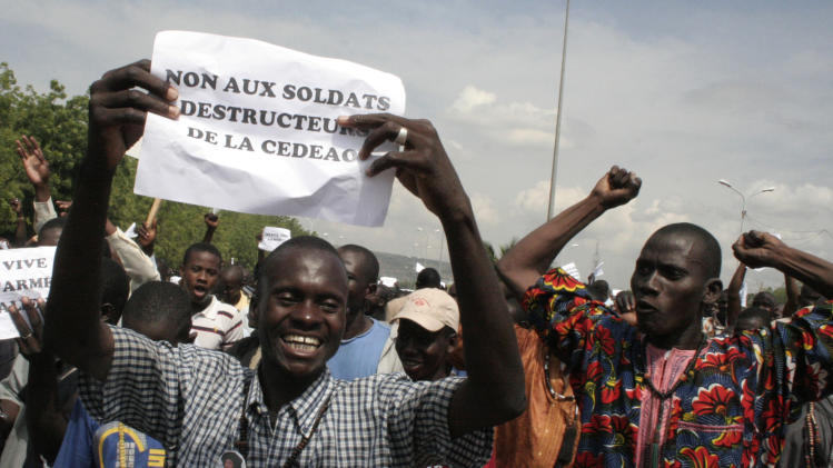 "FILE - A Thursday, Oct. 18, 2012 photo from files showing a man carrying a sign reading ""No to the destructive soldiers of ECOWAS"" as Malians opposed to a military intervention to retake Mali's Islamist-controlled north march in the streets of the capital, Bamako, Mali. Two land-locked, desperately poor African countries many Americans would struggle to find on a map are both gripped by rebellions in the north that have left huge chunks of both nations outside of government control. So why are neighbors rushing troops into Central African Republic after only a few weeks, while Mali is still awaiting military help from its region nearly one year after its political chaos began? (AP Photo/Harouna Traore, File)"
