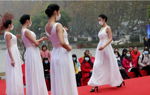 Models wearing masks present jewellery on a runway at a jewellery fair on a hazy day in Nanjing, Jiangsu province