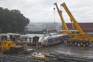 Part of the wreckage of the crashed train is seen in a crane depository on the outskirts of Santiago de Compostela, Spain, Sunday July 28, 2013. Spain's interior minister Jorge Fernandez Diaz says the driver whose speeding train crashed, killing 78 people, is now being held on suspicion of negligent homicide. The Spanish train derailed at high speed Wednesday killing 78 and injuring dozens more. (AP Photo/Lalo R. Villar)