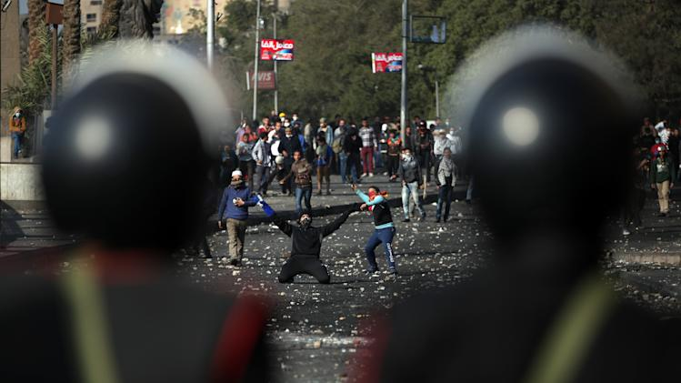 Egyptian protesters clash with riot police near Tahrir Square, Cairo, Egypt, Tuesday, Jan. 29, 2013. Intense fighting for days around central Tahrir Square engulfed two landmark hotels and forced the U.S. Embassy to suspend public services on Tuesday. (AP Photo/Khalil Hamra)
