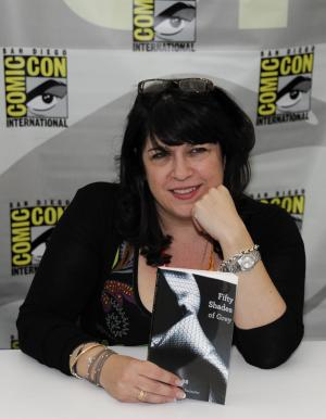 "Author E.L. James poses with her book ""Fifty Shades of Grey"" at a book signing during the first day of Comic-Con convention held at the San Diego Convention Center on Thursday July 12, 2012, in San Diego.  (Photo by Denis Poroy/Invision/AP)"