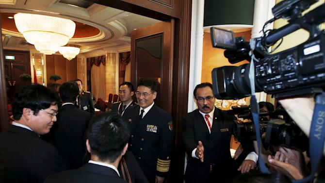 China's Admiral Sun Jianguo shakes hands with members of the Japanese delegation as they meet for a bilateral ahead of the International Institute for Strategic Studies (IISS) Shangri-La Dialogue in Singapore